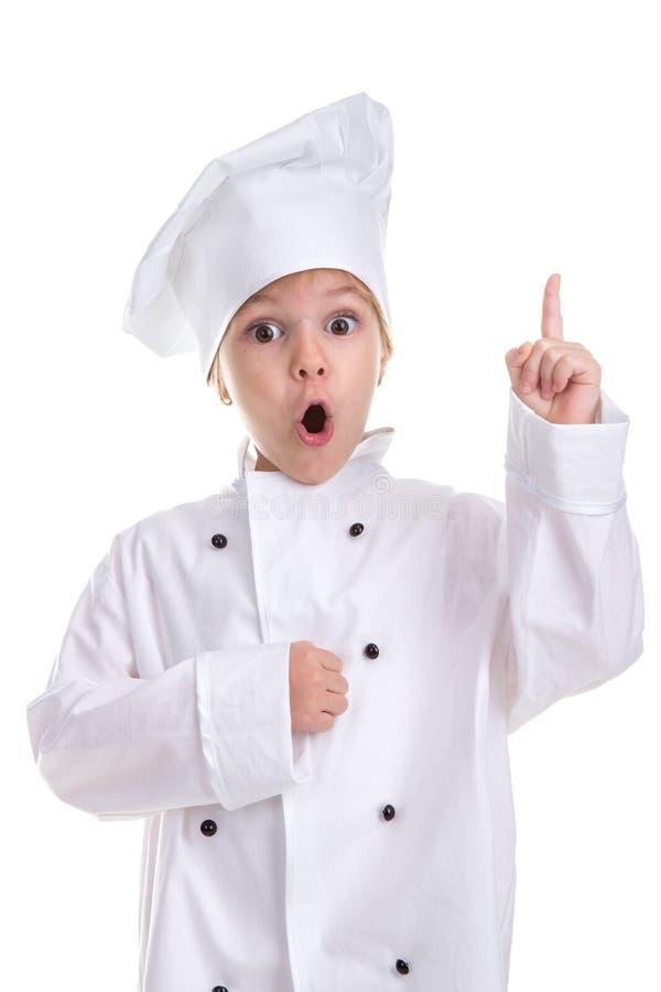 在白色背景隔绝的惊奇的女孩厨师白色制服,看直接与一个poining的手指的照相机 库存图片