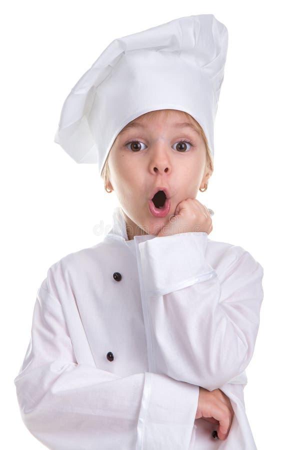 在白色背景隔绝的惊奇的女孩厨师白色制服,看直接照相机,握手下 免版税库存图片