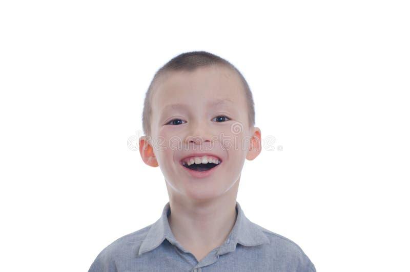 在白色背景隔绝的愉快的微笑的男孩画象 逗人喜爱的可爱的童颜的幸福童年 库存照片