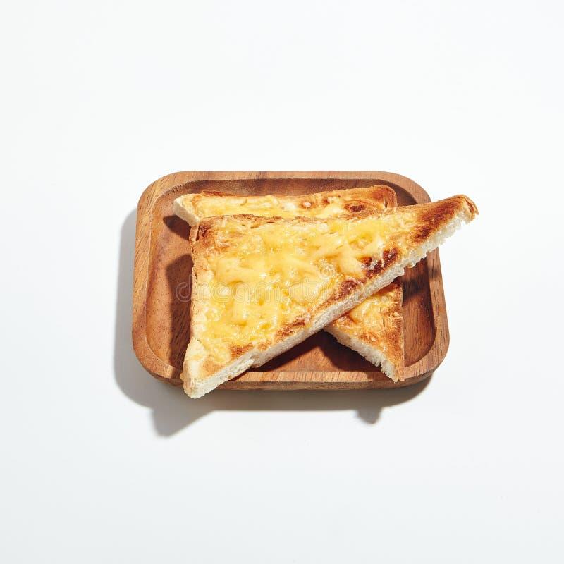 在白色背景隔绝的木板材的乳酪多士 库存图片