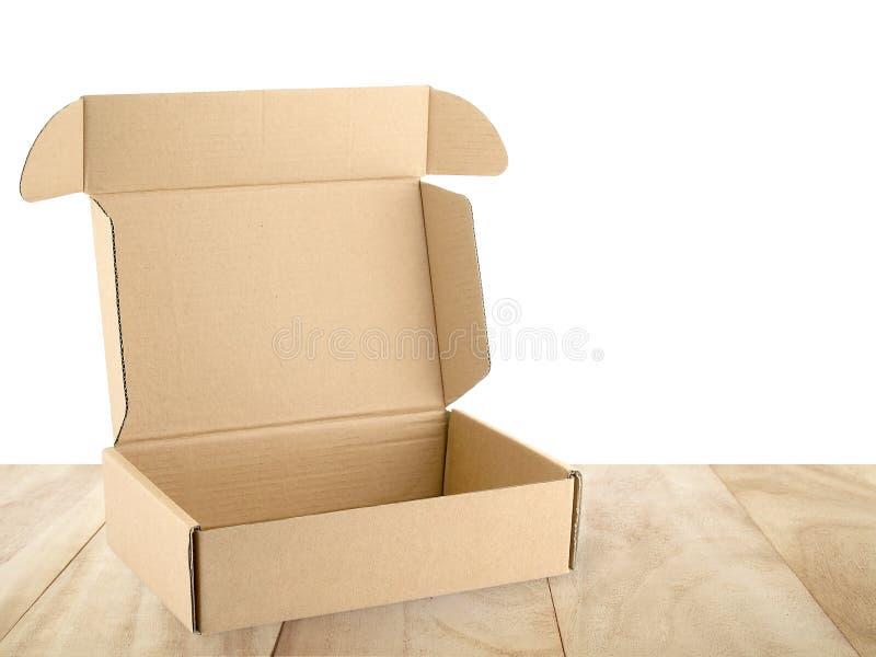 在白色背景隔绝的木桌上的特写镜头开放空的棕色纸盒箱子 免版税库存照片