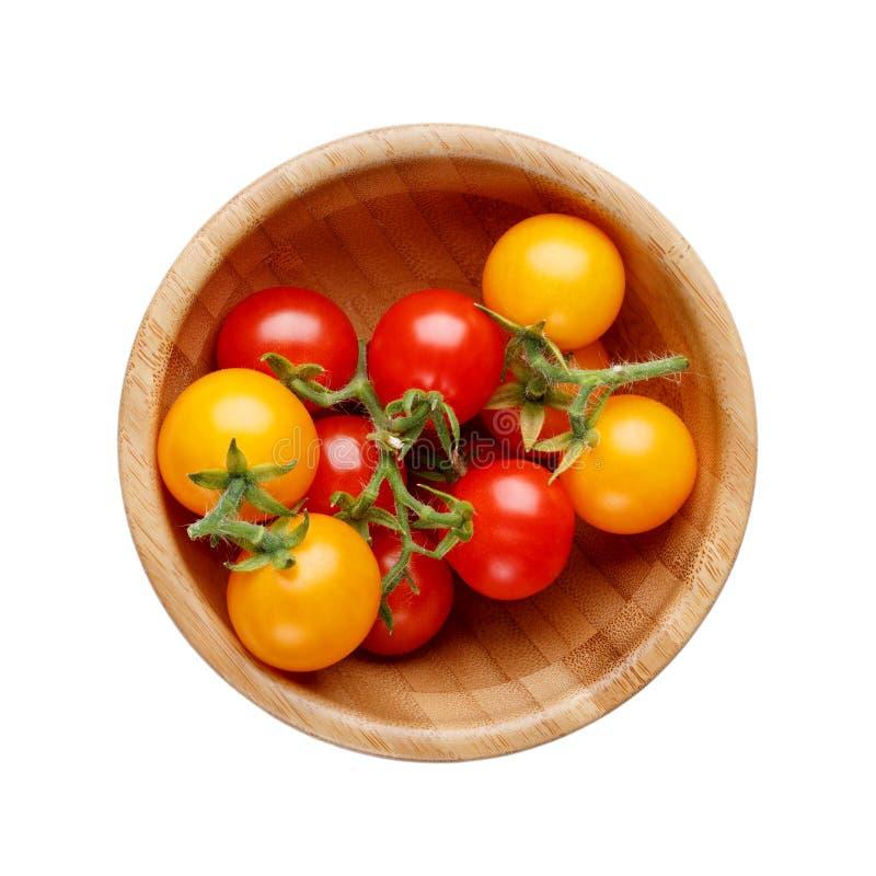 在白色背景隔绝的木碗的红色和黄色小西红柿 免版税库存照片