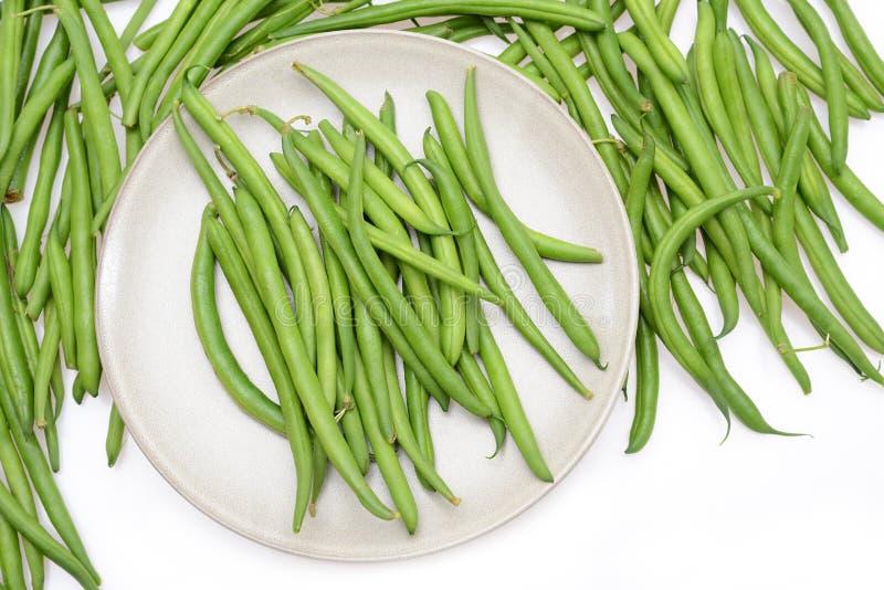 在白色背景隔绝的板材的新鲜的绿色菜豆 免版税库存照片