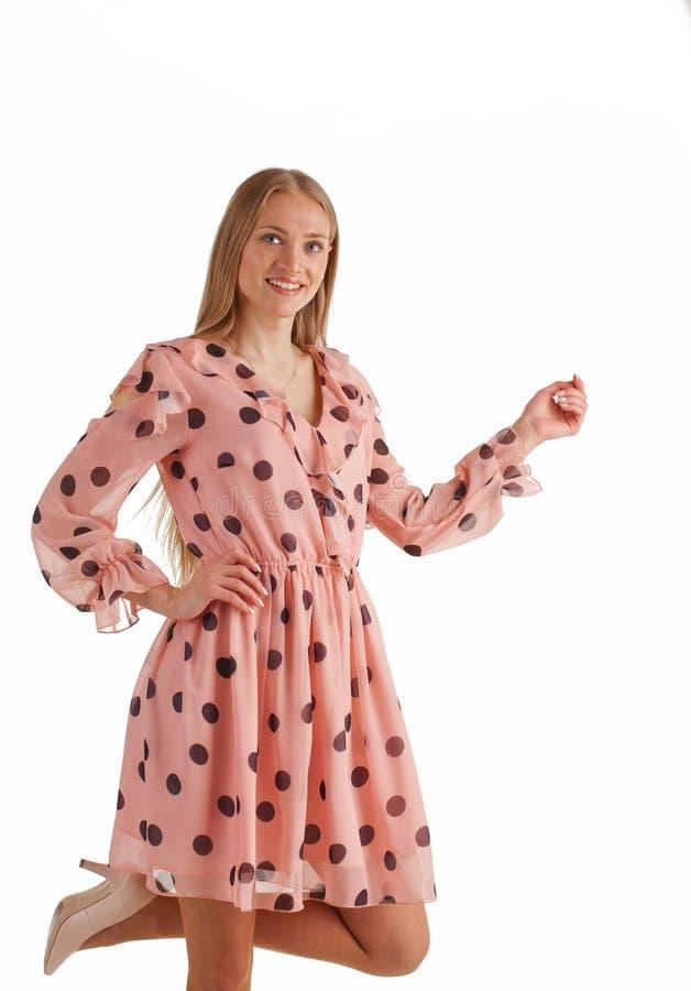 在白色背景隔绝的桃红色礼服的美丽的年轻白肤金发的妇女 免版税库存图片