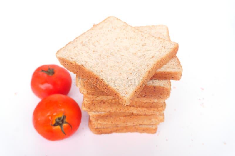 在白色背景隔绝的棕色切的全麦面包的关闭 健康自创三明治早餐准备 免版税图库摄影