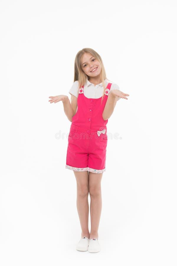 在白色背景隔绝的流行粉红连衫裤的女孩 微笑的孩子佩带的夏天成套装备 孩子用手我穿上` t 库存图片