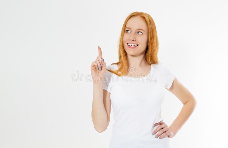 在白色背景隔绝的照片微笑的红色头发夫人指向她的在尤里卡标志的手指,有巨大创新想法, 免版税库存照片