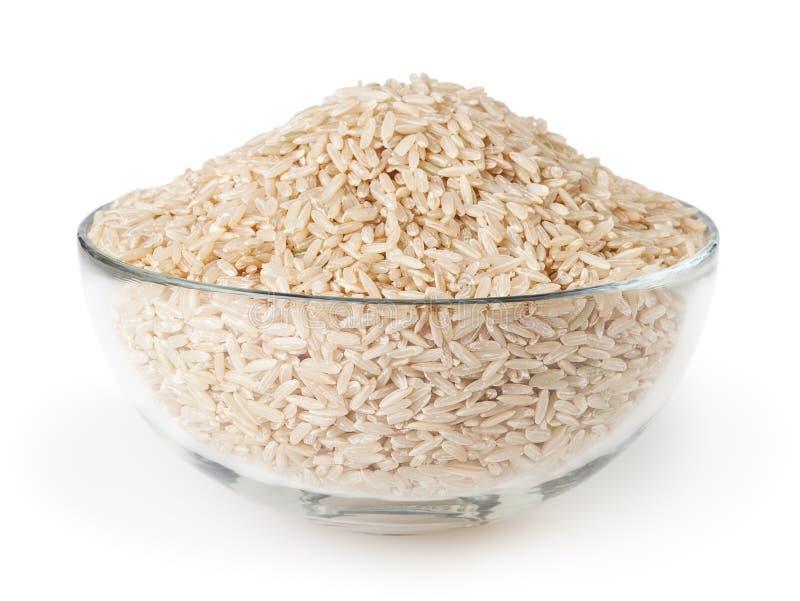 在白色背景隔绝的玻璃碗的未煮过的糙米 库存图片