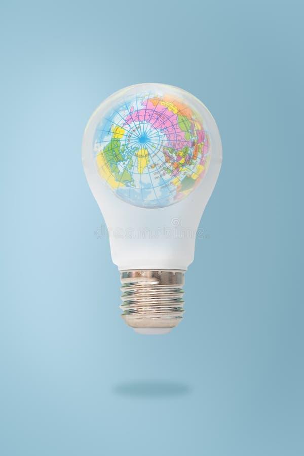 在白色背景隔绝的电灯泡的蓝色世界地图,象征环境关心或绿色能量 免版税库存图片