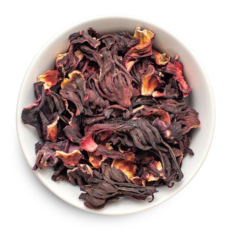 在白色背景隔绝的碗的干木槿瓣 红色茶,karkade r 库存照片