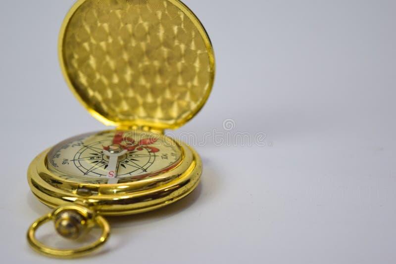 在白色背景隔绝的磁性金黄指南针的关闭 库存照片