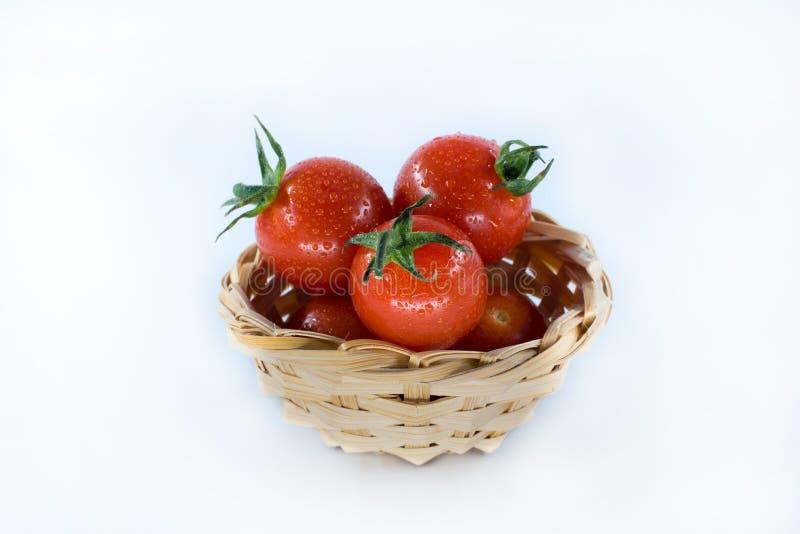 在白色背景隔绝的篮子的群蕃茄 免版税库存照片