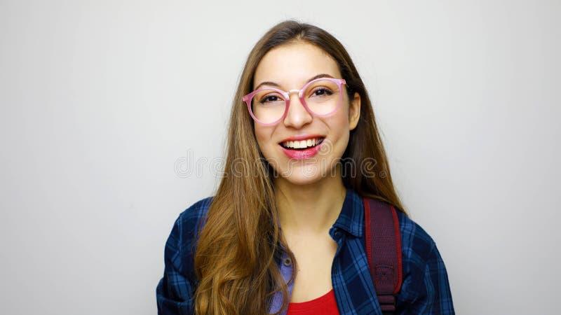 在白色背景隔绝的精力充沛的书呆子少年女孩画象愉快地笑,好象期望友好的会议或 免版税图库摄影