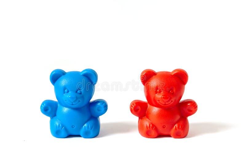 在白色背景隔绝的红色和蓝色塑料玩具熊 免版税库存照片