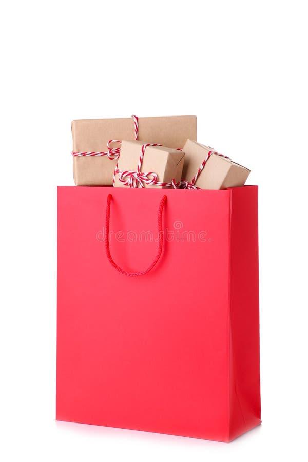 在白色背景隔绝的红色纸袋的礼物盒,购物的概念 库存图片
