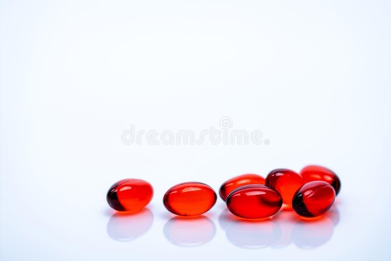 在白色背景隔绝的红色软的胶凝体胶囊药片 堆红色软的明胶胶囊 维生素和膳食补充剂 库存图片