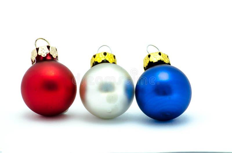 在白色背景隔绝的红色,白色和蓝色圣诞节装饰品 免版税库存照片