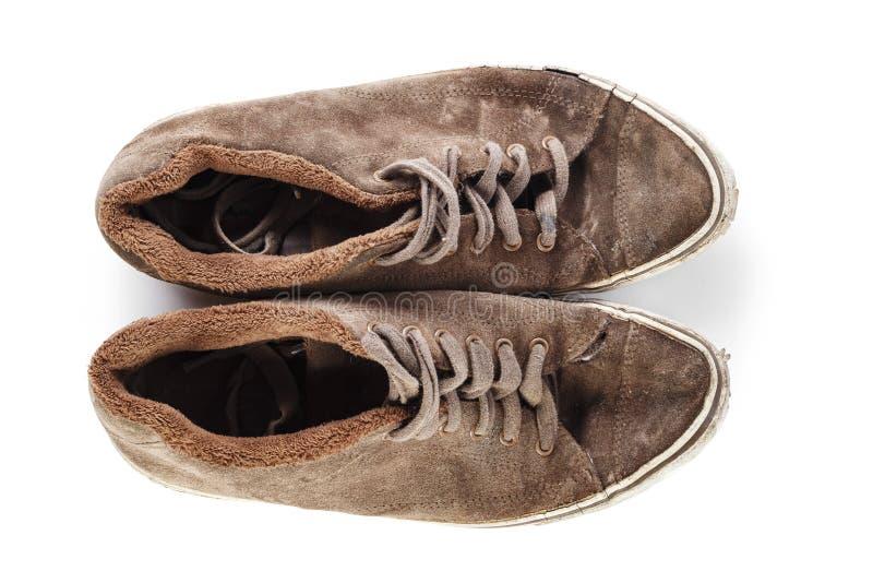 在白色背景隔绝的老和肮脏的棕色运动鞋 库存图片