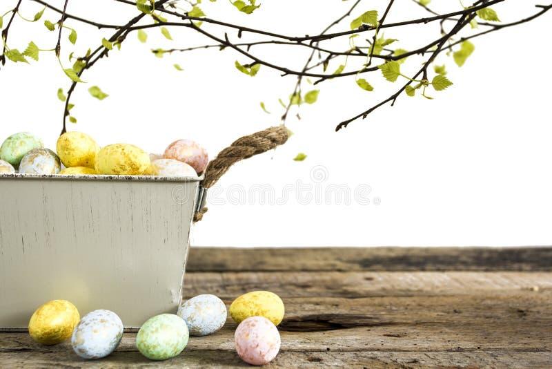 在白色背景隔绝的老木桌上的复活节彩蛋 库存照片