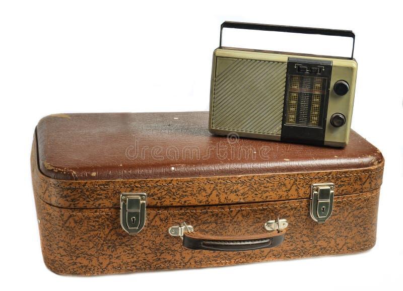 在白色背景隔绝的老皮革手提箱的减速火箭的无线电接收机 免版税库存照片
