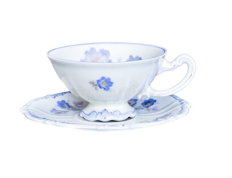 在白色背景隔绝的茶碟的典雅的瓷茶杯 免版税库存照片