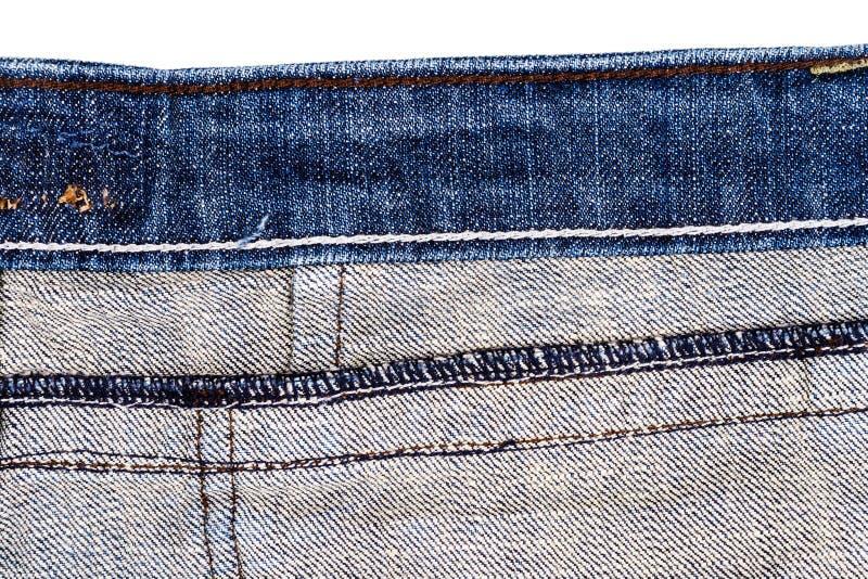 在白色背景隔绝的蓝色牛仔裤织品片断 概略的参差不齐的边缘 被撕毁的牛仔布牛仔裤 免版税图库摄影