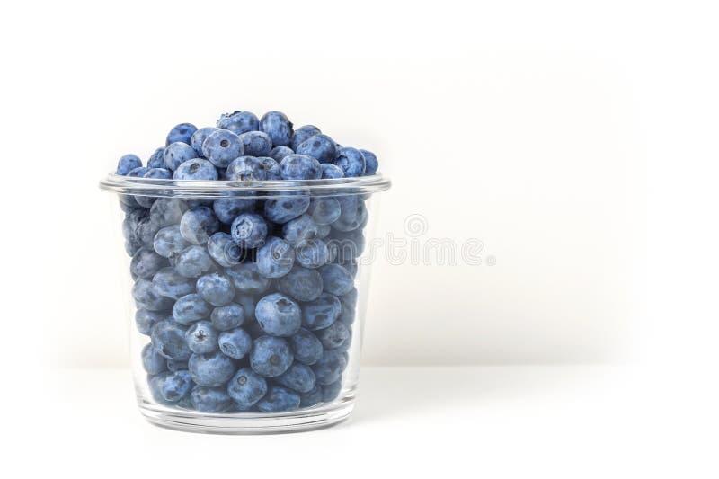 在白色背景隔绝的透明玻璃碗的新鲜的有机蓝莓 在罐的甜鲜美越桔 夏天 免版税库存照片
