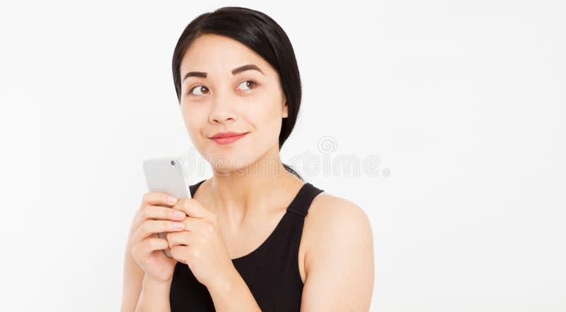 在白色背景隔绝的逗人喜爱的愉快的亚洲女孩举行电话 免版税库存照片