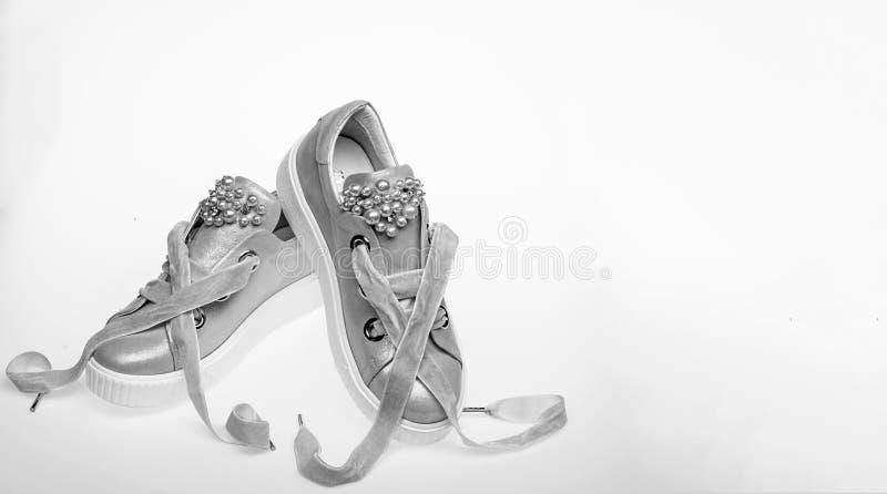 在白色背景隔绝的逗人喜爱的鞋子,拷贝空间 用珍珠和妇女的鞋类装饰的女孩成串珠状 对  免版税库存图片