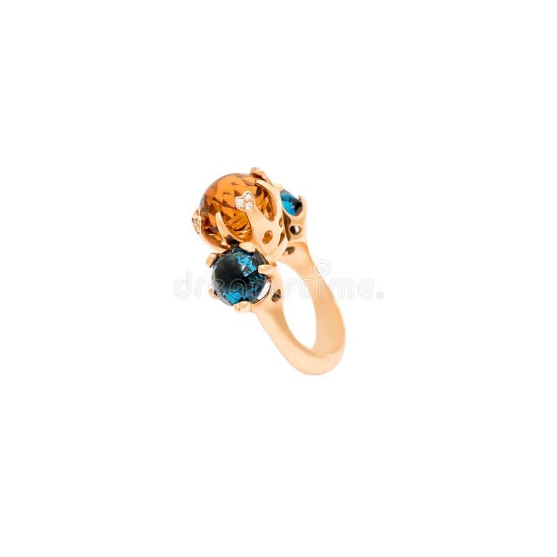 在白色背景隔绝的金黄钻戒 与金刚石和珍贵的颜色宝石的圆环 豪华首饰 免版税库存照片