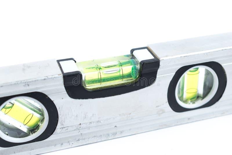 在白色背景隔绝的银色水平仪 建筑室内漆滚筒工具墙壁 金属小精神杠杆 修理工具 库存图片