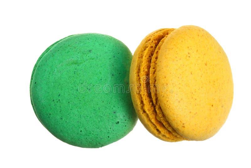 在白色背景隔绝的黄色和绿色macaron,不用阴影特写镜头 顶视图 平的位置 库存照片