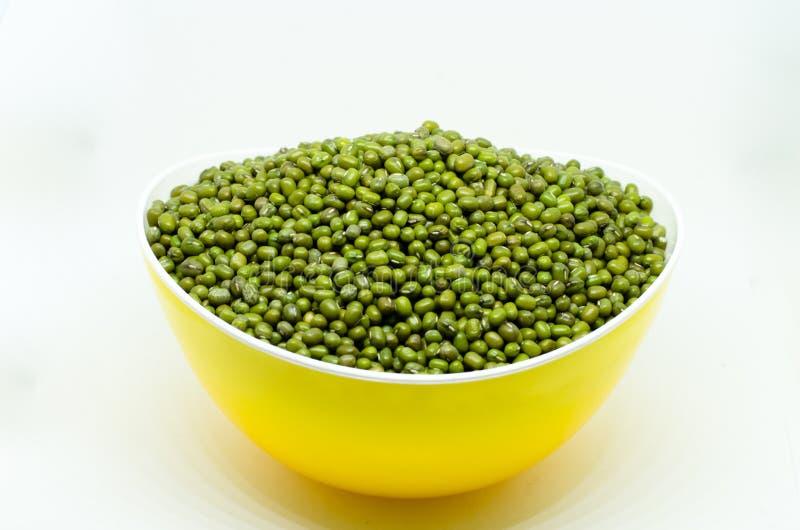 在白色背景隔绝的黄色碗的绿豆 免版税库存图片