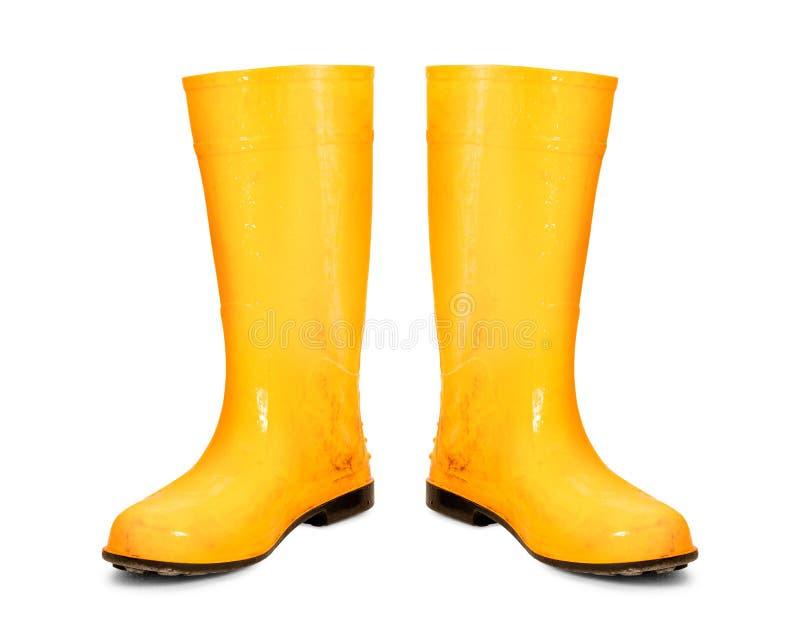 在白色背景隔绝的黄色胶靴 肮脏的起动 图库摄影
