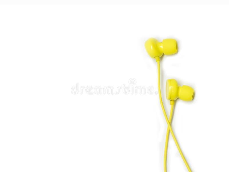 在白色背景隔绝的黄色earbuds 免版税库存图片