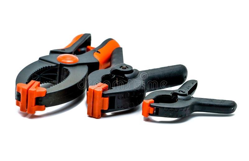 在白色背景隔绝的黑和橙色春天钳位 套塑料钳位的小,中等和大大小 夹紧工具 库存照片