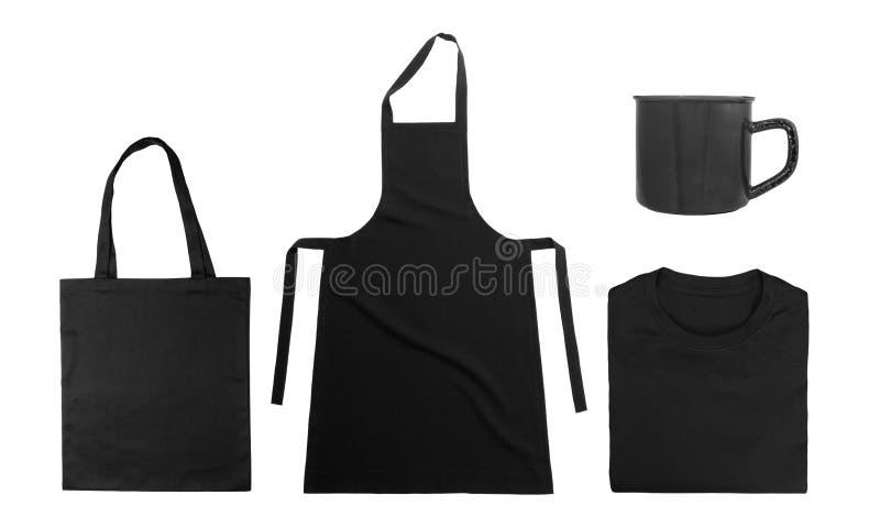 在白色背景隔绝的黑对象的汇集 黑棉花袋子,黑被折叠的T恤杉,厨房围裙,金属 库存图片
