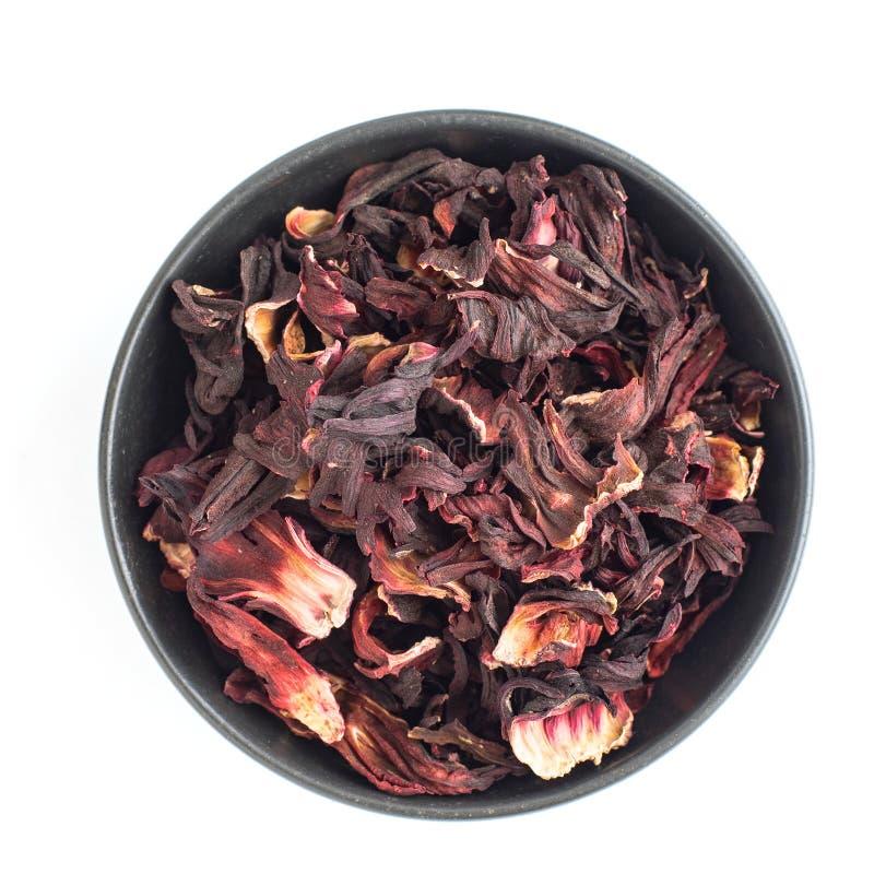 在白色背景隔绝的黑暗的碗的干木槿瓣 红色茶,karkade r 免版税库存图片
