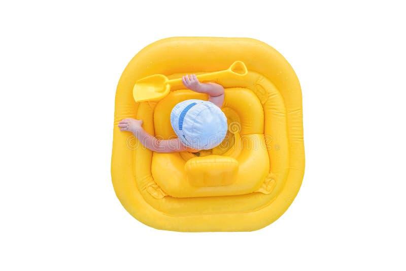 在白色背景隔绝的一艘黄色可膨胀的木筏的婴孩 库存图片