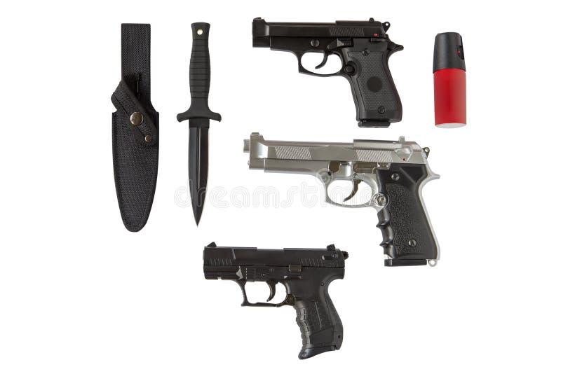 在白色背景隔绝的手枪、刀子和胡椒喷洒器 库存照片