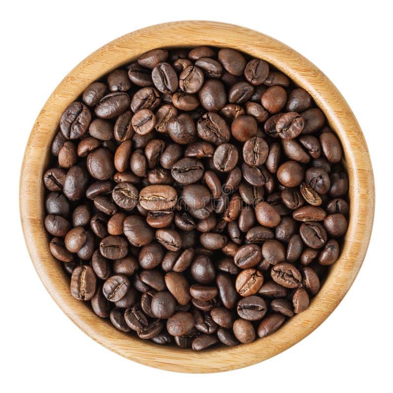 在白色背景隔绝的木碗的烤咖啡豆 图库摄影
