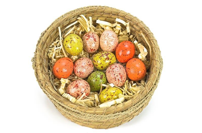 在白色背景隔绝的棕色篮子的五颜六色的被绘的复活节彩蛋 免版税图库摄影
