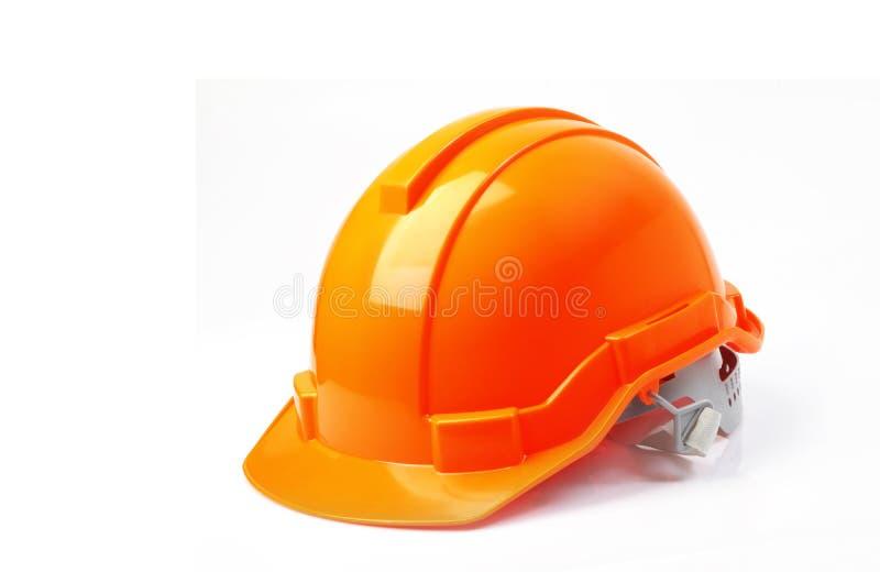 在白色背景隔绝的橙色安全帽,在w的安全帽 图库摄影