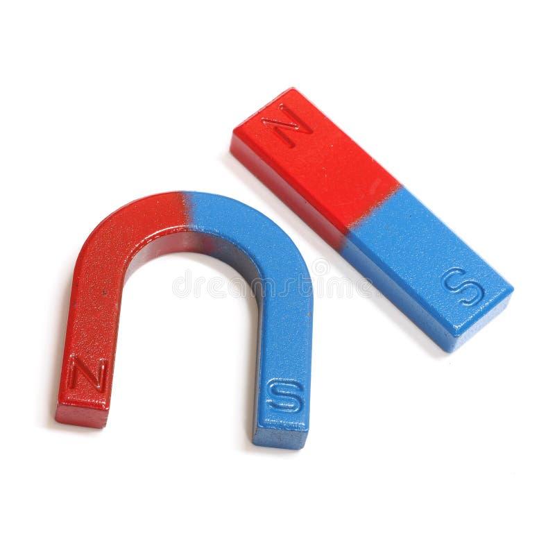 在白色背景隔绝的红色和蓝色马掌磁铁 库存照片