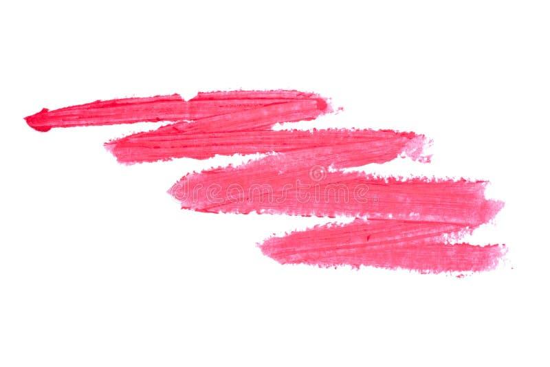 在白色背景隔绝的红色唇膏污点 被弄脏的构成产品样品 免版税库存照片