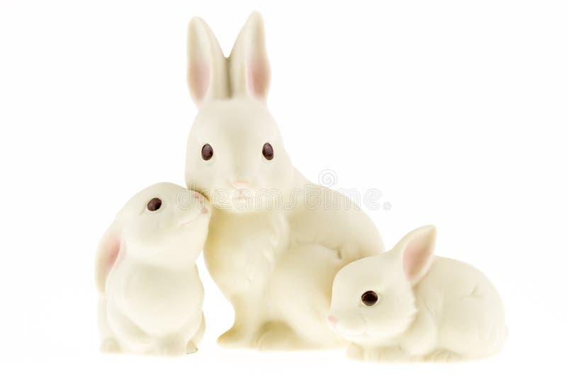 在白色背景隔绝的陶瓷兔宝宝家庭。 库存图片