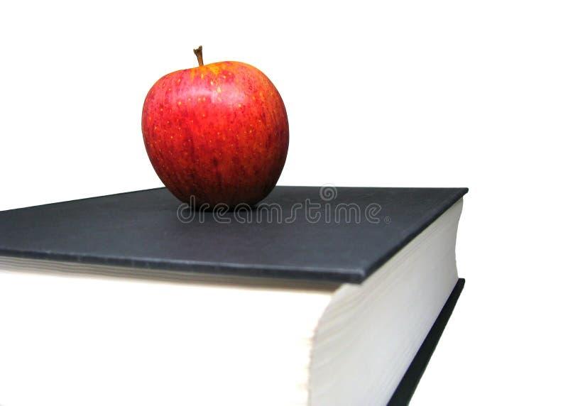 在白色背景隔绝的黑精装书字典书顶部的红色苹果 图库摄影