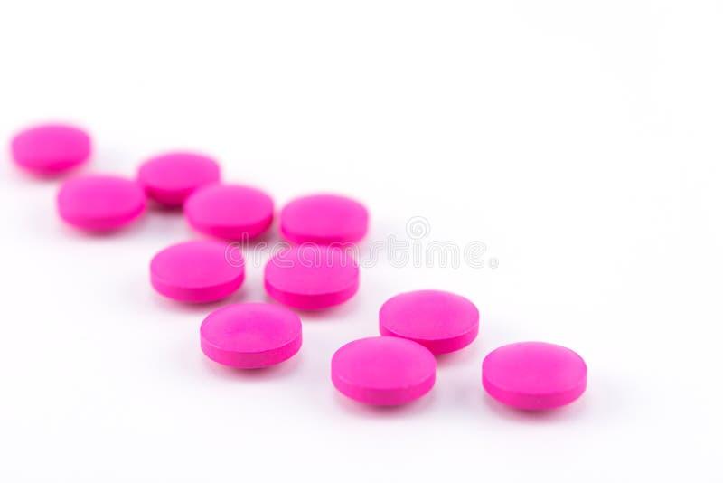 在白色背景,医疗概念的桃红色圆的药片 免版税库存照片