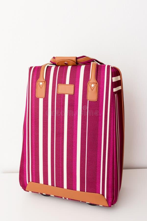 在白色背景,最小的旅行概念的红色和白色镶边行李袋子 免版税图库摄影