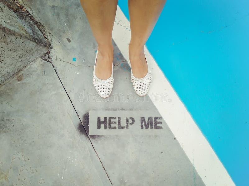 在白色芭蕾舞鞋的妇女的脚在题字对面-帮助我 概念-失去的游人 免版税库存照片